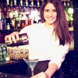 Zusammengesetztes Bild des Porträts des Barmixers blaues Martini-Getränk im Glas gießend Stockfotografie