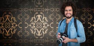 Zusammengesetztes Bild des Porträts des glücklichen Fotografen Digitalkamera halten Stockfotos