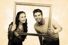 Zusammengesetztes Bild des Porträts des glücklichen Paars Bilderrahmen halten Lizenzfreie Stockbilder