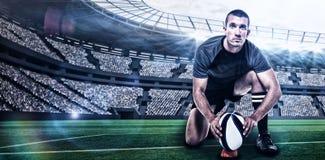 Zusammengesetztes Bild des Porträts des Rugbyspielers im schwarzen Trikot, das Ball mit 3d setzt Stockfoto