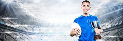 Zusammengesetztes Bild des Porträts des lächelnden Rugbyspielers, der Trophäe und Ball hält lizenzfreie stockfotos