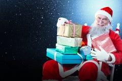 Zusammengesetztes Bild des Porträts von nettem Weihnachtsmann Weihnachtsgeschenke auf Stuhl halten Stockfotografie