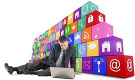 Zusammengesetztes Bild des reifen Geschäftsmannes sitzend unter Verwendung des Laptops Stockbild