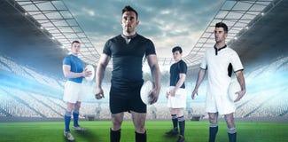 Zusammengesetztes Bild des Rugbyspielers Rugbyball halten lizenzfreie stockfotos