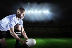Zusammengesetztes Bild des Rugbyspielers schauend weg beim Halten des Balls auf dem Treten des T-Stücks lizenzfreie stockbilder