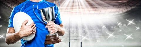 Zusammengesetztes Bild des Rugbyspielers Trophäe und Ball halten lizenzfreies stockfoto