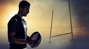 Zusammengesetztes Bild des ruhigen denkenden Rugbyspielers beim Halten des Balls Stockfotos