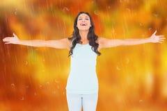 Zusammengesetztes Bild des sorglosen Brunette mit den Armen heraus Stockbilder