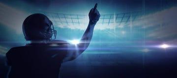 Zusammengesetztes Bild des Spielers des amerikanischen Fußballs im Sturzhelm aufwärts zeigend lizenzfreie stockfotografie