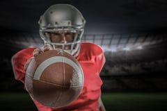 Zusammengesetztes Bild des Spielers des amerikanischen Fußballs im roten Trikot, das Ball hält Lizenzfreies Stockbild