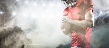 Zusammengesetztes Bild des Spielers des amerikanischen Fußballs im roten Trikot, das den Ball wirft Stockfotos