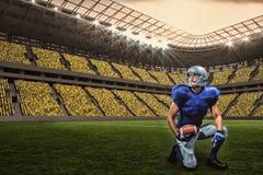 Zusammengesetztes Bild des Spielers des amerikanischen Fußballs mit Ball kniend mit 3d Stockbilder