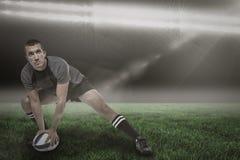Zusammengesetztes Bild des Sportspielers im schwarzen Trikot, das mit Ball 3d ausdehnt Stockfotos