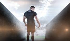 Zusammengesetztes Bild des starken Rugbyspielers, der Ball hält Lizenzfreie Stockfotografie