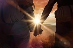 Zusammengesetztes Bild des stehenden Händchenhaltens der Trampenpaare auf der Straße lizenzfreies stockbild