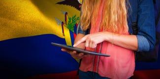 Zusammengesetztes Bild des Studenten, der Tablette in der Bibliothek verwendet Stockbild