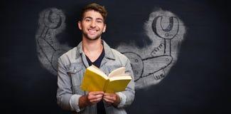 Zusammengesetztes Bild des Studenten lächelnd an der Kamera in der Bibliothek lizenzfreie stockfotos