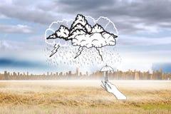 Zusammengesetztes Bild des Sturmgekritzels mit der Hand, die kleinen Regenschirm hält Stockbild