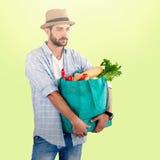 Zusammengesetztes Bild des tragenden Gemüses des Mannes in der Einkaufstasche gegen weißen Hintergrund Stockbilder