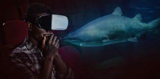 Zusammengesetztes Bild des tragenden Kopfhörers der virtuellen Realität des Mannes im Theater lizenzfreies stockfoto