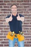 Zusammengesetztes Bild des tragenden Werkzeuggurtes des Mannes, während das Darstellen herauf Zeichen abgreift Stockbild