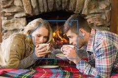 Zusammengesetztes Bild des trinkenden Tees der romantischen Paare vor beleuchtetem Kamin Lizenzfreies Stockbild