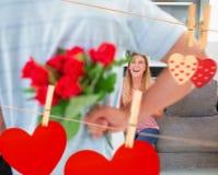Zusammengesetztes Bild des versteckenden Blumenstraußes des Mannes der Rosen von lächelnder Freundin auf der Couch Lizenzfreie Stockfotos