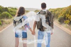 Zusammengesetztes Bild des Wanderns von den Paaren, die auf Landschaftsstraße stehen Stockfotografie