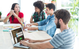 Zusammengesetztes Bild des zufälligen Geschäftsmannes schreibend auf seinem Laptop Lizenzfreie Stockfotografie