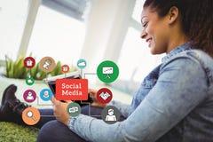 Zusammengesetztes Bild Digital der Frau, die Tablet-Computer durch verschiedene Ikonen verwendet Stockbilder