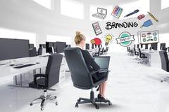 Zusammengesetztes Bild Digital der Geschäftsfrau, die Laptop mit Brandingtext und Ikonen im Büro verwendet Stockbilder