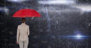 Zusammengesetztes Bild Digital der Geschäftsfrau roten Regenschirm bei der Stellung halten im Regen Stockfotos