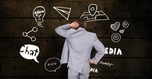 Zusammengesetztes Bild Digital des verwirrten Geschäftsmannes verschiedene Ikonen betrachtend gegen hölzerne Wand Stockfotos