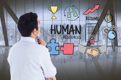 Zusammengesetztes Bild Digital des verwirrten Geschäftsmannes verschiedene Ikonen im Büro betrachtend Stockbild