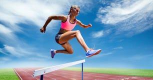 Zusammengesetztes Bild Digital des weiblichen Athleten springend über die Hürde stockfotografie
