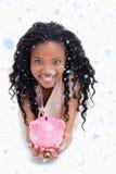 Zusammengesetztes Bild einer jungen Frau, die an der Kamera lächelt, hält ein Sparschwein in ihren Händen Lizenzfreie Stockbilder