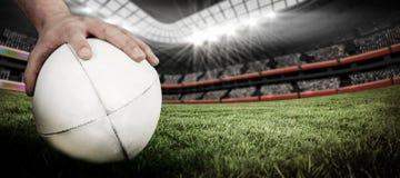 Zusammengesetztes Bild eines Rugbyspielers, der einen Rugbyball aufwirft Stockfotografie