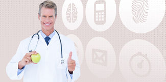 Zusammengesetztes Bild lächelnden männlichen Doktors, der grünen Apfel beim Daumen sich zeigen hält Stockfoto