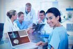 Zusammengesetztes Bild schönen lächelnden Doktors, der auf Tastatur mit ihrem Team hinten schreibt Stockfoto