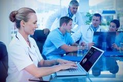 Zusammengesetztes Bild schönen lächelnden Doktors, der auf Tastatur mit ihrem Team hinten schreibt Lizenzfreie Stockbilder