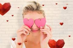Zusammengesetztes Bild von attraktiven jungen blonden haltenen Herzen über Augen Lizenzfreie Stockfotografie