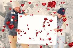 Zusammengesetztes Bild von attraktiven Paaren im Winter arbeiten das Zeigen des Plakats um Lizenzfreie Stockfotos