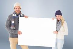 Zusammengesetztes Bild von attraktiven Paaren im Winter arbeiten das Zeigen des Plakats um Stockbild