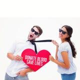 Zusammengesetztes Bild von Brunette ihren Freund durch die Bindung ziehend, die Herz hält Lizenzfreies Stockfoto