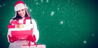 Zusammengesetztes Bild von Brunette im Winter kleidet das Halten vieler Geschenke und Einkaufstaschen Lizenzfreies Stockfoto
