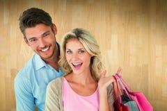 Zusammengesetztes Bild von den attraktiven jungen Paaren, die Einkaufstaschen halten Stockfoto