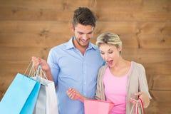Zusammengesetztes Bild von den attraktiven jungen Paaren, die Einkaufstaschen halten Lizenzfreie Stockfotografie