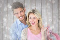 Zusammengesetztes Bild von den attraktiven jungen Paaren, die Einkaufstaschen halten Stockfotografie
