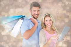 Zusammengesetztes Bild von den attraktiven jungen Paaren, die Einkaufstaschen unter Verwendung des Tabletten-PC halten Lizenzfreies Stockfoto