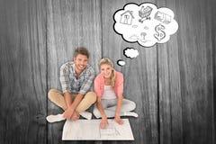 Zusammengesetztes Bild von den attraktiven jungen Paaren, die Plan betrachtend sitzen lizenzfreies stockbild